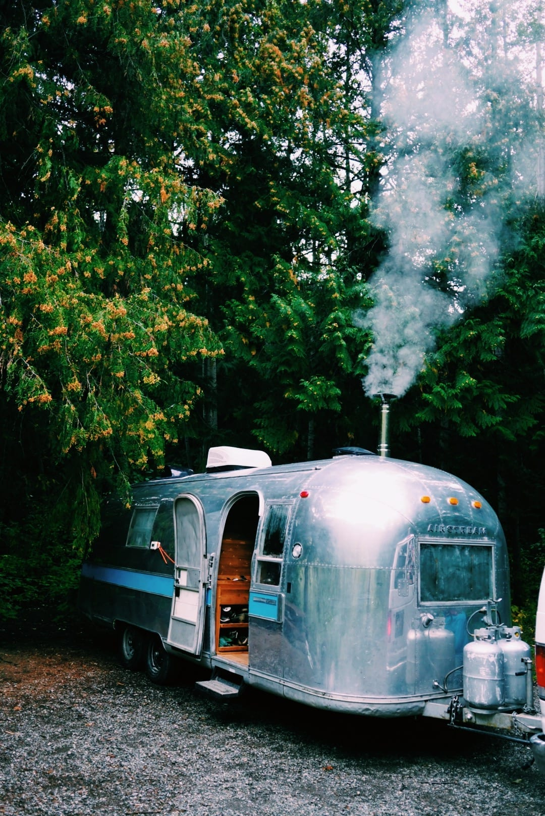 Airstream in the forest wiht Tiny Wood Stove flue